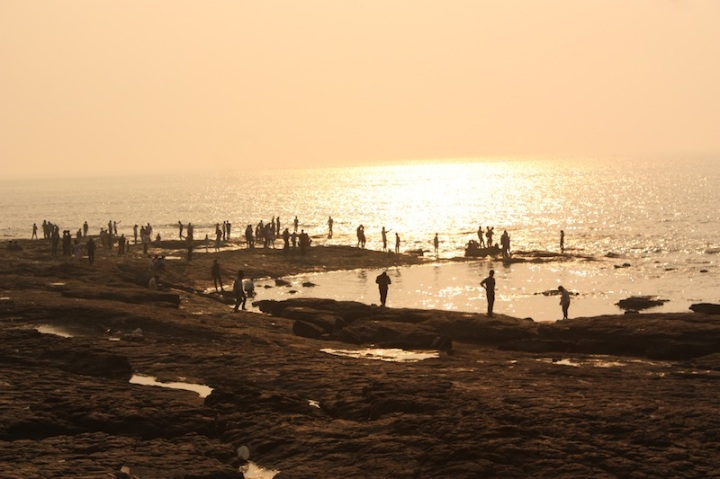 the sun sets in the sea at bandra bandstand