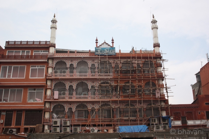 In a line of similar looking buildings squashed together, Jama Masjid stands out with its minarets and painted work shining against the pink.